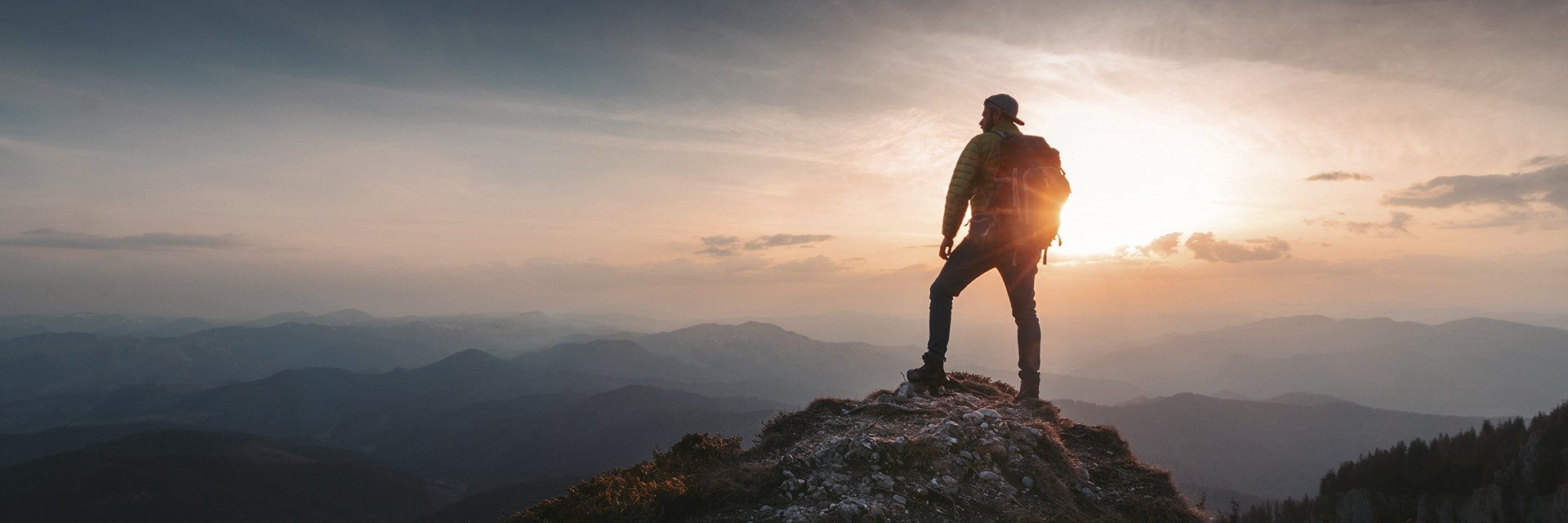 man standing at the top of a mountain looking out over the landscape