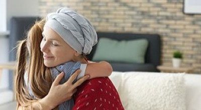 woman with cancer hugging child